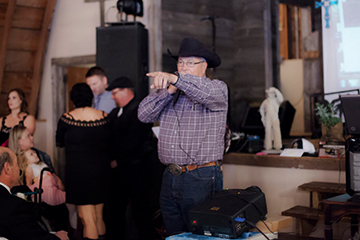 Dale Pahlke auctioneering for blue jean black tie affair